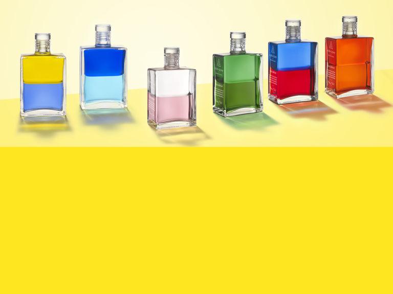 Aura-Soma Flaschen über einer gelben Farbfläche